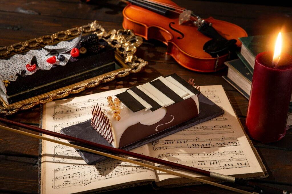 ヘーゼルナッツのダックワーズにコーヒームースとメープル風味のマスカルポーネの「不協和音のレクイエム」は、 まるでピアノの鍵盤のような見た目に仕上げた。ヴァローナのグラン・クリュ・テロワール マンジャリを用いたダークチョコレートムースにバラを利かせたラズベリージャムを配した「オナーズ・ウィッチの証」は、優秀な魔女が身に着ける制服を彷彿とさせる。